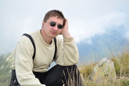 expects: A young man sits on a hilltop and looking thoughtfully into the distance Stock Photo