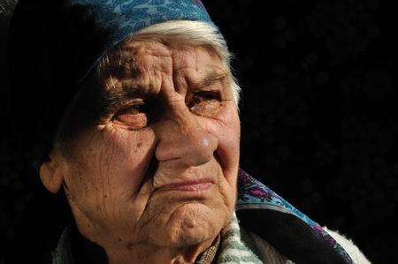 sad old woman: La mujer triste, vieja, mirando de lejos, aislado de fondo negro