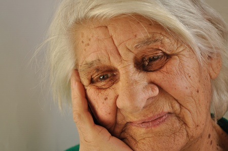 leaned: Elderly gray-haired woman with a sad thought, leaned her cheek on his hand