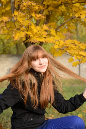 strand of hair: Young red-haired girl holding a strand of hair
