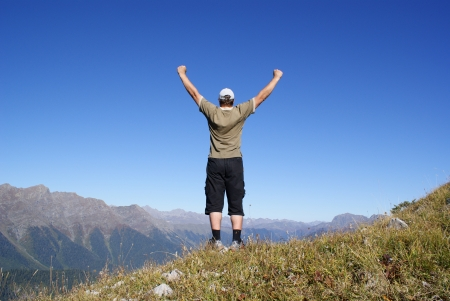 A man stands on a hillside with their hands up photo