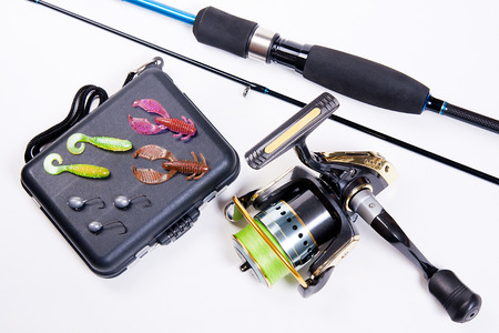 Fishing rod and reel with box for baits on white. Fishing silicone lures. photo