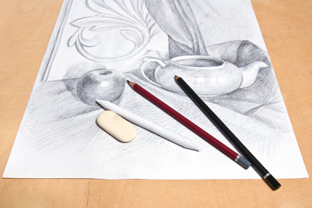 Drawing of naturmort by graphite pencil with apple, tea infuser and plaster palm leaf. Graphite pencils, eraser and paper stump on the wooden background.