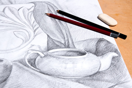 Drawing of still life by graphite pencil with apple, tea infuser and plaster palm leaf. Graphite pencils and eraser on the wooden background. Stock Photo