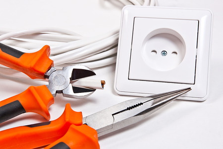 wall socket: Close up view of the wall socket, power cable and electrician tools on white background