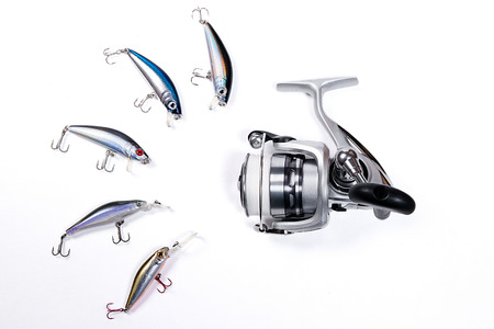 baits: Fishing reel with plastic fishing baits on the white background. Stock Photo