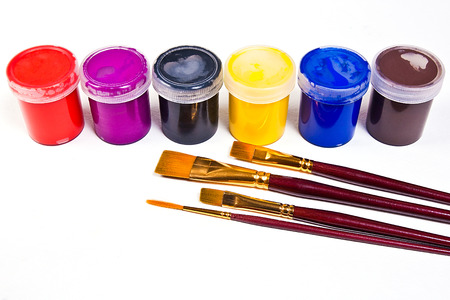 Bottles with gouache paints and different kinds of brushes for artistic paintings on the white background.