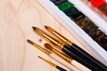 aquarelle: Close up view of the professional aquarelle paints in box with brushes on the wooden background.