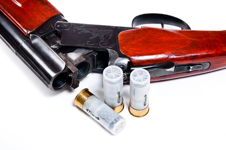 hunting: Hunting shotgun and ammunition on white background. Cartridges for hunting rifle. Close up view showing mechanism of hunting rifle. Isolated on white.