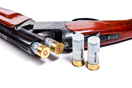 sports shell: Hunting shotgun and ammunition on white background. Cartridges for hunting rifle. Close up view showing mechanism of hunting rifle. Isolated on white.