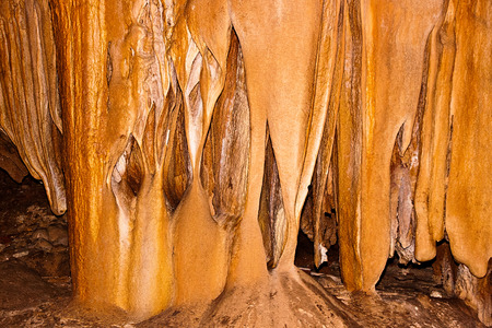 Inside view of an underground cavern or cave with stalagmites and stalactites. Limestone formations on the wall of an underground cave. Stalactite and stalagmite formations in the cave. Stock Photo