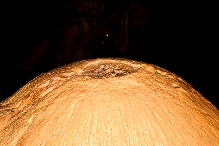 drop ceiling: Inside view of an underground cavern or cave with stalagmites and stalactites. Limestone formations on the wall of an underground cave. Drop of water in small pool on the limestone formations of an underground cave.