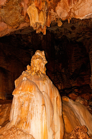 caving: Inside view of an underground cavern or cave with stalagmites and stalactites. Limestone formations on the wall of an underground cave. Stalactite and stalagmite formations in the cave. Stock Photo