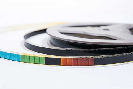 cine: A reel of motion picture film on a white background. Old film strip isolated on white background.