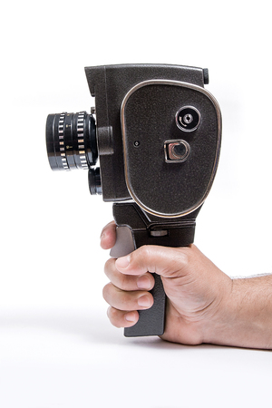 filmmaker: Old movie camera with lens in hand isolated on a white background.