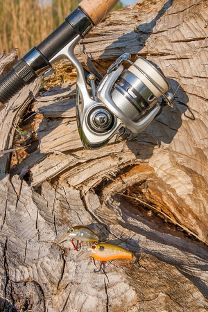 sportfishing: Fishing rod with fishing reel on the natural background. Assorted of various kind of fishing baits. Spinning on the old tree with brown bark.