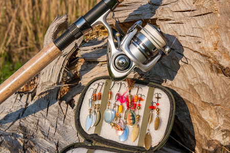 sharp: Fishing rod with fishing reel on the natural background. Assorted of various kind of fishing baits. Spinning on the old tree with brown bark.