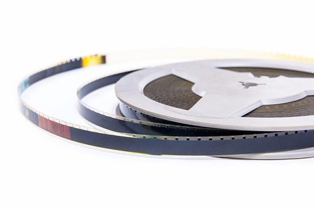 motion picture: A reel of motion picture film on a white background. Old film strip isolated on white background.