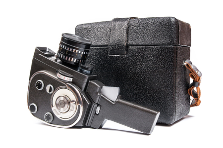 Old movie camera with lens and black leather case isolated on a white background.