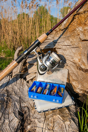 Fishing rod with fishing reel on the natural background. Assorted of various kind of fishing baits. Spinning on the old tree with brown bark.