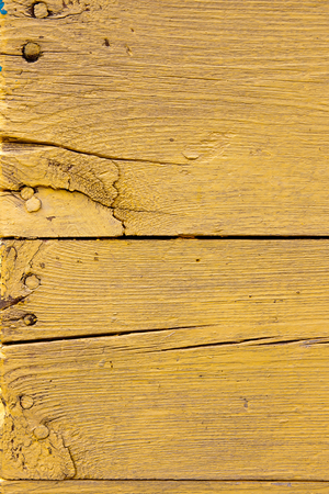 upkeep: Wood texture with painting color peeled off. Flaking yellow paint - wood background texture. Stock Photo