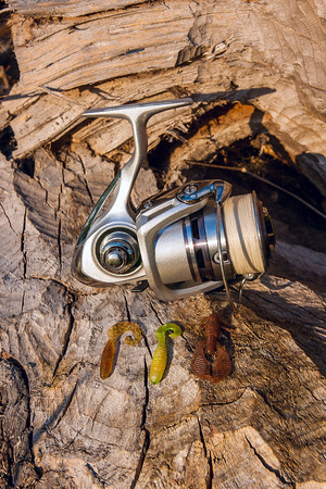 sportfishing: Fishing reel on the natural background. Assorted of various kind of fishing baits. Spinning on the old tree with brown bark. Stock Photo