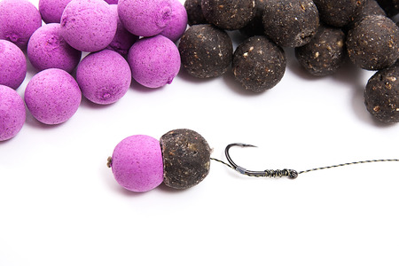 fishing rig: Close up view of fishing baits and Fishing gear for carp. Accessories for carp fishing. View of ready for use fishing hook with carp boilies, dry feed for carp fishing and different boilies isolated on white background. Stock Photo