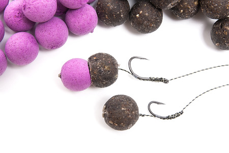 feed up: Close up view of fishing baits and Fishing gear for carp. Accessories for carp fishing. View of ready for use fishing hook with carp boilies, dry feed for carp fishing and different boilies isolated on white background. Stock Photo
