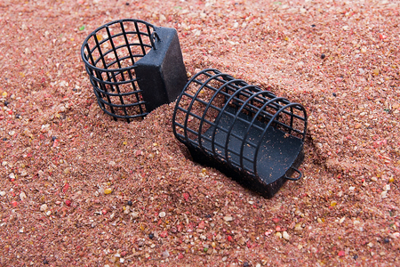 feed up: Close up view of fishing feeder. Dry feed for carp fishing as background for different fishing feeder.