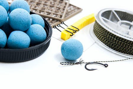 fishing rig: Close up view of fishing baits and Fishing gear for carp. Accessories for carp fishing. View of fishing hook, dry feed for carp fishing and different boilies isolated on white background. Stock Photo