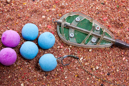 feed up: Close up view of fishing baits and Fishing gear for carp. Dry feed for carp fishing as background for carp bait with fishing flat feeder for carp fishing. Stock Photo