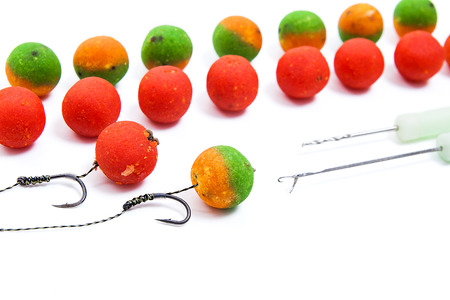 fishing rig: Close up view of fishing baits and Fishing gear for carp. Accessories for carp fishing. View of fishing hook and different boilies isolated on white background. Stock Photo