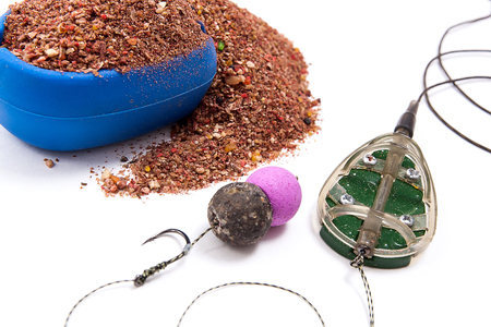 feed up: Close up view of fishing baits and Fishing gear for carp. Dry feed for carp fishing. Ready for use carp bait with fishing flat feeder for carp fishing isolated on white background. Stock Photo