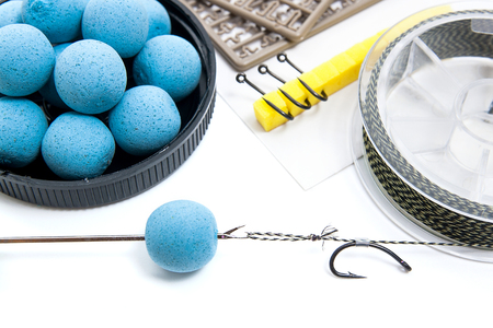 feed up: Close up view of fishing baits and Fishing gear for carp. Accessories for carp fishing. View of fishing hook, dry feed for carp fishing and different boilies isolated on white background. Stock Photo