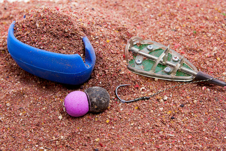 fishing rig: Close up view of fishing baits and Fishing gear for carp. Dry feed for carp fishing as background for carp bait with fishing flat feeder for carp fishing. Stock Photo