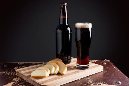 Glas mit dunklem Bier und volle Flasche Bier auf dunklem Hintergrund. Scheiben geräucherter Käse auf Schneidebrett.