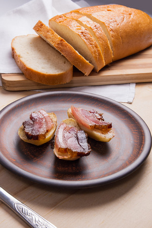 eating utensils: Tasty baked potatoes with slices of bacon in brown clay plate on wooden background. Slices of smoked bacon on potatoes. Slices of white bread on cutting board. Eating utensils fork and knife near with plate.