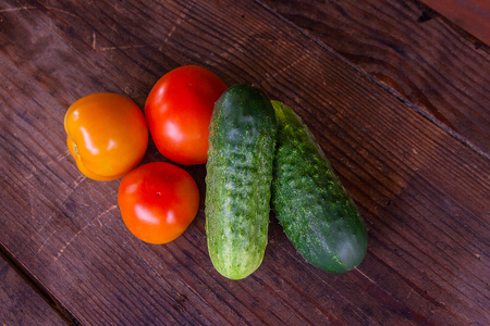Freshly picked whole red ripe tomatoes and cucumbers on the wooden background  Zdjęcie Seryjne