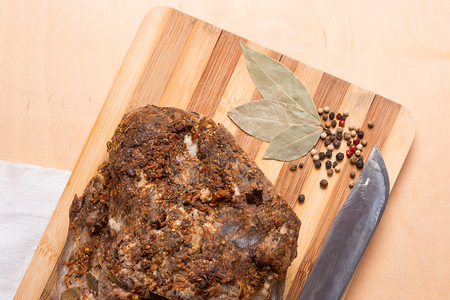 Spicy meat baked with herbs and spice on wooden cutting board. Country style oven-baked spicy ham. A juicy fresh baked pork and pepper with bay leaves on on wooden board.  Stock Photo