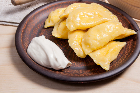 Fresh boiled homemade ukrainian dumplings with cottage cheese or curd and butter on clay plate and with sour cream on wooden background. Varenyky or dumplings or pierogi is a traditional ukrainian meal. Rolling pin and sieve on brown cloth - rustic style.