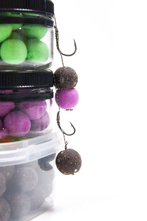 hook up: Close up view of fishing baits and Fishing gear for carp. Accessories for carp fishing. View of ready for use fishing hook with carp boilies, dry feed for carp fishing and different boilies isolated on white background.
