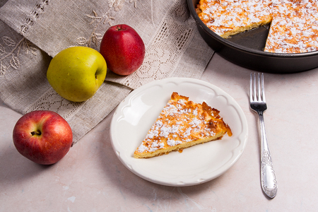 white backing: Slice of homemade apple pie with fork on white plate. Homemade freshly baked apple pie in backing form with apples. Several organic red and green apples in the background.
