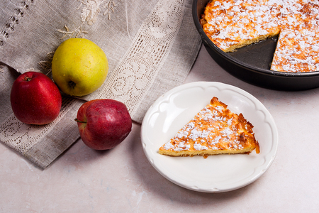 white backing: Slice of homemade apple pie with fresh apples on white plate. Homemade freshly baked apple pie in backing form with apples. Several organic red and green apples in the background.