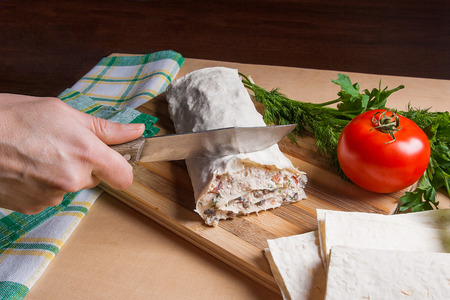 Woman hand with knife in it cutting thin Armenian pita bread or lavash wrapped tomatoes, cottage cheese or curd, chicken meat, tomatoes and herbs - dill, onion, parsley on cutting board. Red ripe tomato, lavash and herbs - dill, green onion, parsley. Comp