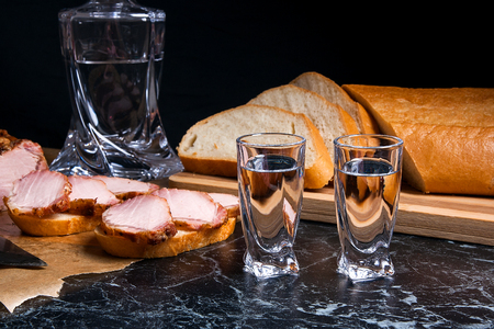 cold cut: Bottle and shot glasses with vodka. Small snack of bread and meat near the shot glass. Slices of smoked meat or ham on brown packing paper. White wheat bread on wooden cutting board. Composition on black marble background.