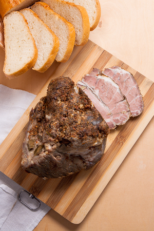 Spicy meat baked with herbs and spice on wooden cutting board. Country style oven-baked spicy ham. A juicy fresh baked pork on wooden board and slices white wheat bread in yellow wooden basket. Stock Photo