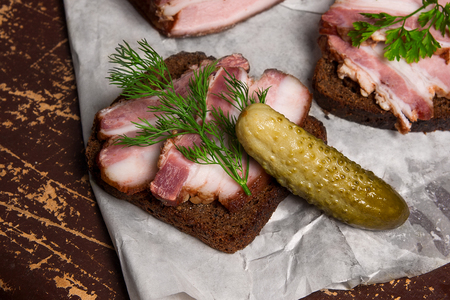 Close up view slices of smoked bacon on the piece rye bread with herbs and several pickles - rustic style on brown vintage background.