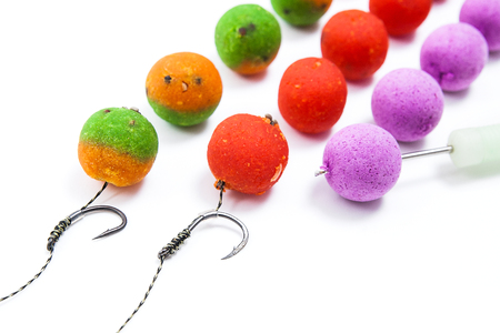 fishing rig: Close up view of fishing baits and Fishing gear for carp. Accessories for carp fishing. View of fishing hook and different boilies isolated on white background.