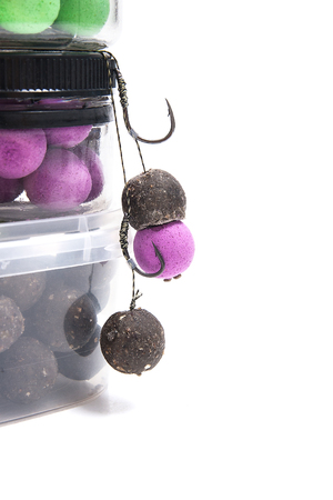 fishing rig: Close up view of fishing baits and Fishing gear for carp. Accessories for carp fishing. View of ready for use fishing hook with carp boilies, dry feed for carp fishing and different boilies isolated on white background.
