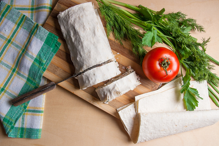 Pieces of cutted thin Armenian pita bread or lavash wrapped tomatoes, cottage cheese or curd, chicken meat, tomatoes and herbs - dill, onion, parsley with vintage knife on cutting board. Red ripe tomato, lavash and herbs - dill, green onion, parsley. Comp